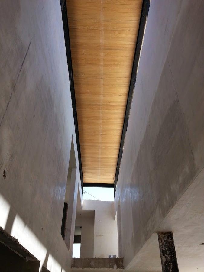 Terminación de techo a doble altura en acabado de duela de madera con vigas IPR