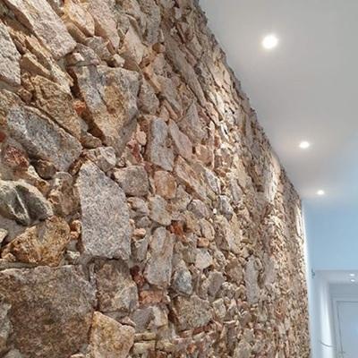 Iluminación de muro de piedra en sala