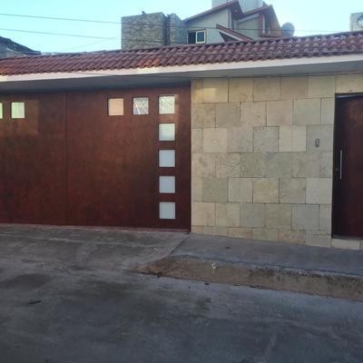Fachada exterior Con portón pintado, Muro con acabado y Techumbre con teja