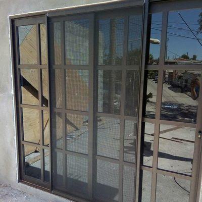 Puerta de patio color chocolate con vidrio grey y mosquitero.