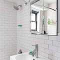 Baño remodelado con azulejos blancos tipo ladrillo