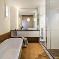 Baño con tina y piso de madera