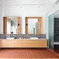 Baño amplio con dos lavamanos, espejos y paneles corredizos de vidrio