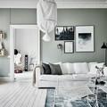 Sala estilo nórdico con sillón grande y cuadros en la pared