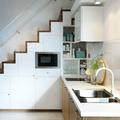 Cocina pequeña con alacenas bajo la escalera