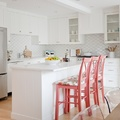 Cocina remodelada con tonos blancos y sillas color coral