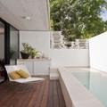 Terraza con piso de madera y alberca pequeña