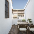 Terraza de estilo mediterráneo con piso y mobiliario de madera
