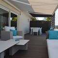 Terraza remodelada con toldos, sillones y piso de madera