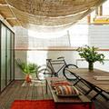 Terraza luminosa con piso de madera y toldos de paja