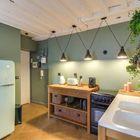 Cocina con paredes pintadas de verde y piso de madera