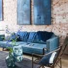Sala con paredes de ladrillo y sillón de terciopelo