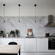 Cocina con pared y barra de mármol