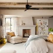 Recámara con chimenea, vigas de madera en el techo y piso laminado