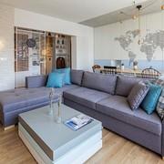 Sala con sillón grande y piso de madera