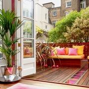 Terraza con cojines de colores y piso de madera