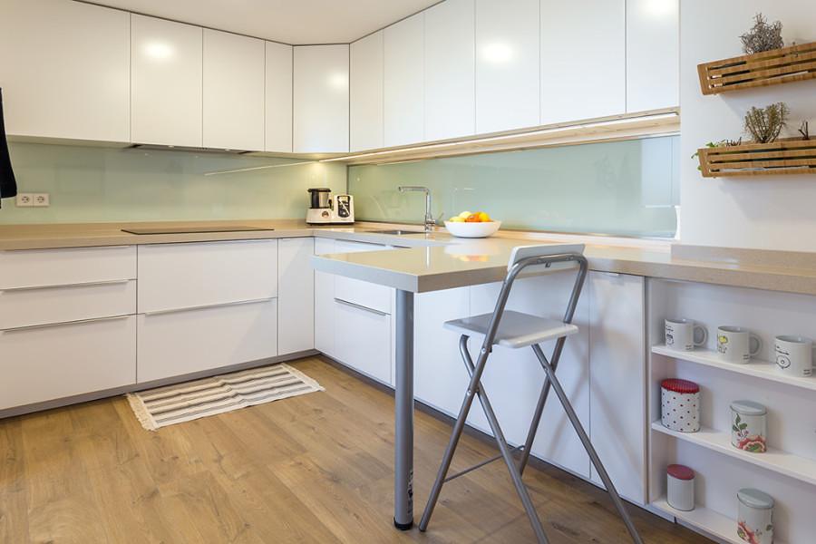Cocina con muebles blancos y piso de madera
