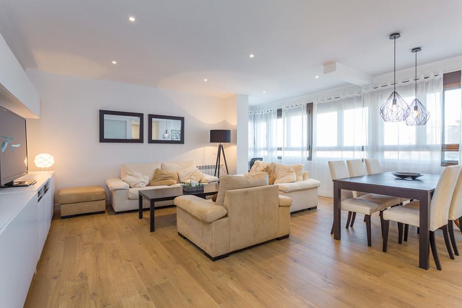 Sala amplia con piso de madera y comedor