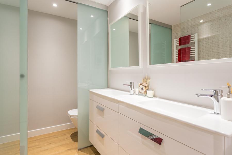 Baño con doble lavabo y puerta corrediza de vidrio