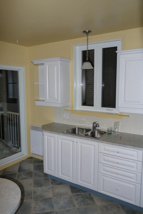 Cocina antigua con muebles blancos y paredes amarillas