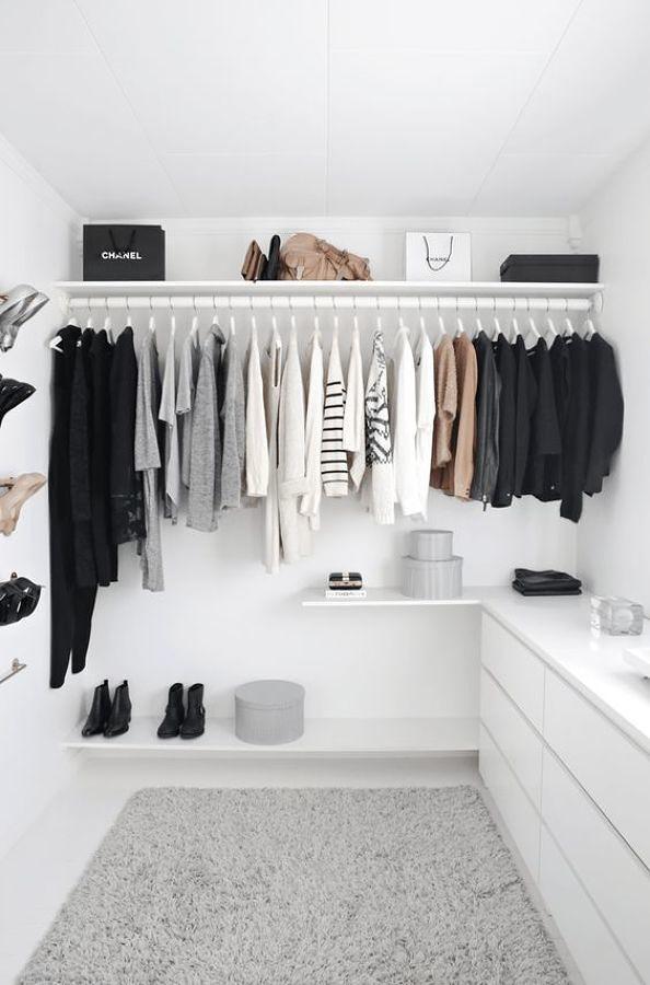 Clóset abierto con ropa colgada y tapete