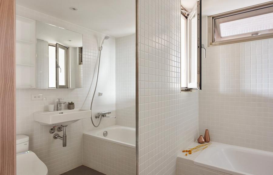 Baño blanco con espejos y azulejos