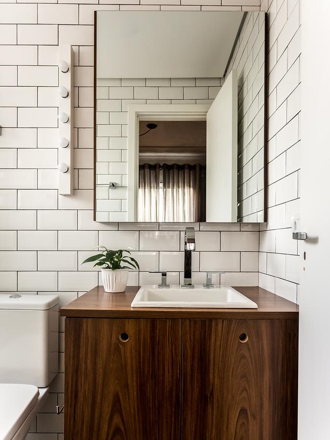 Baño con gabinete de madera y paredes de azulejos