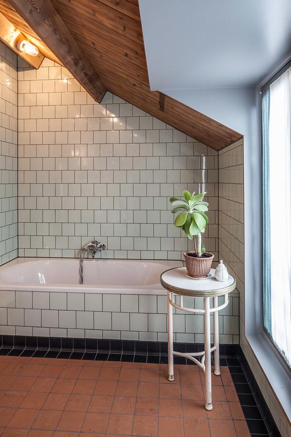 Baño con techo inclinado y revestimiento de azulejos en paredes y piso