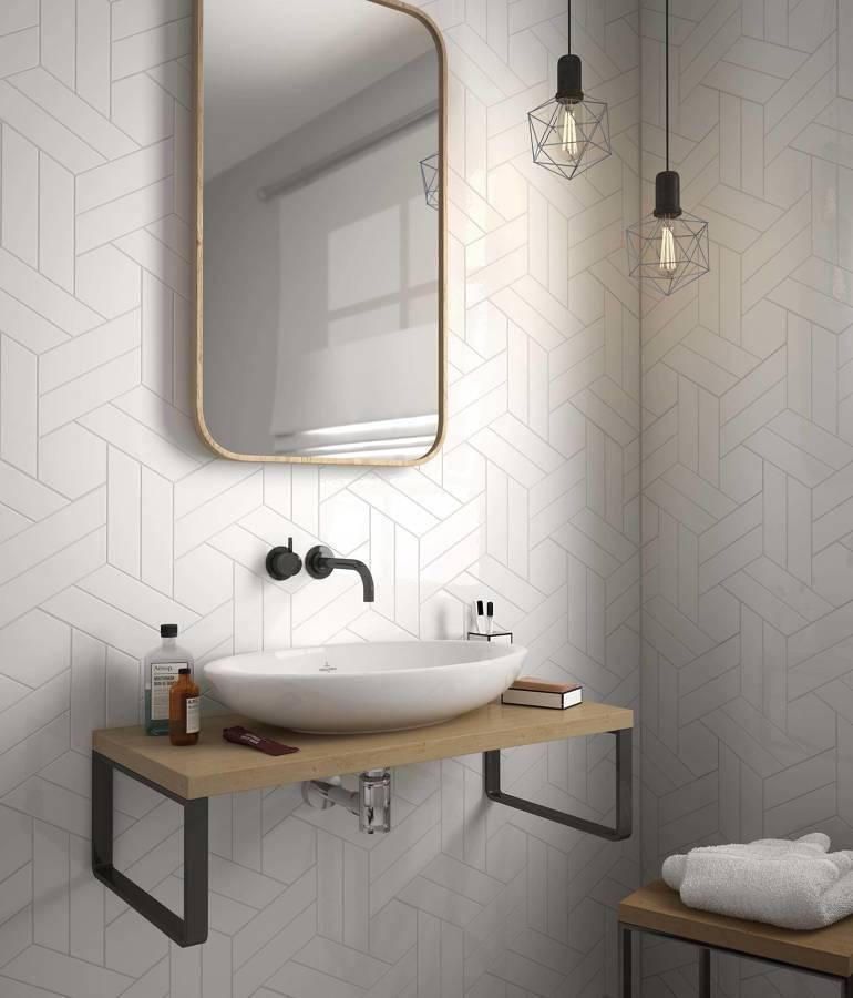 Baño moderno con lavabo y espejo y azulejos con motivos geométricos