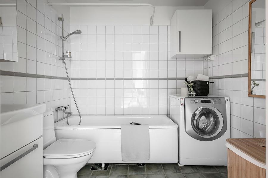 Baño pequeño con azulejos blancos en las paredes