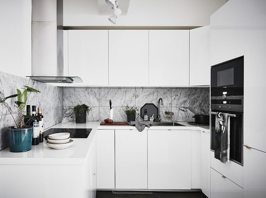 Cocina con mobiliario blanco y campana extractora