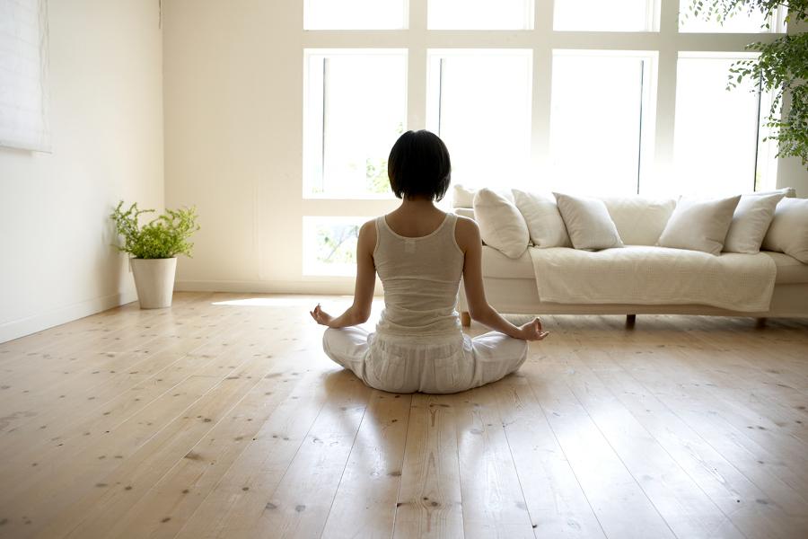 Mujer meditando en el piso de la sala