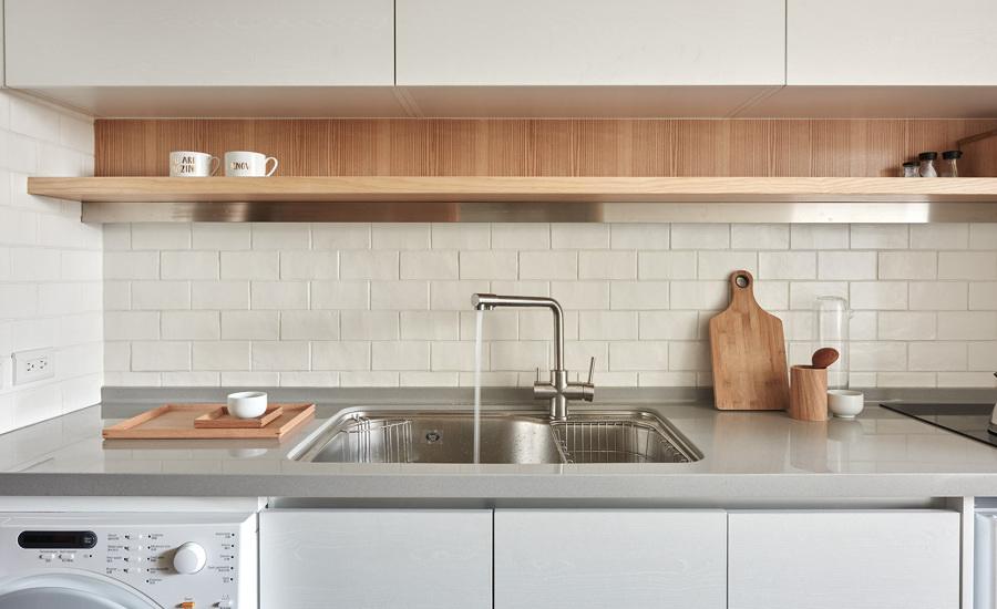 Cocina blanca con barra de cuarzo y estantería de madera