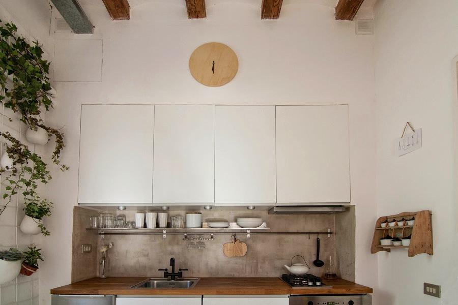 Cocina con alacenas blancas, microcemento y madera