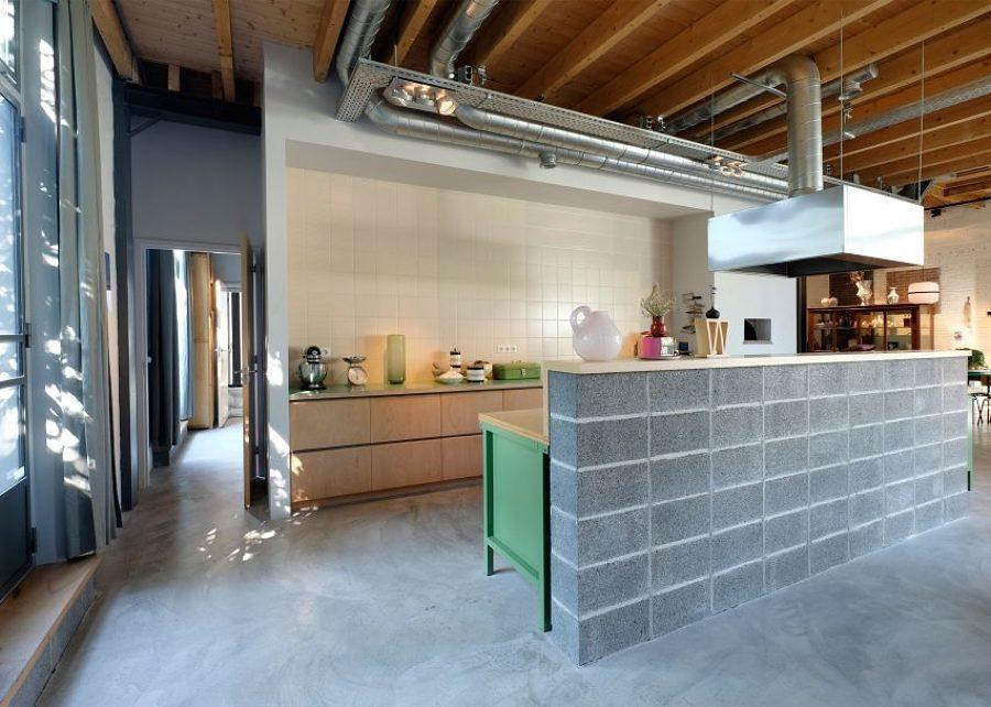 Cocina abierta separada de la sala con bloques de concreto