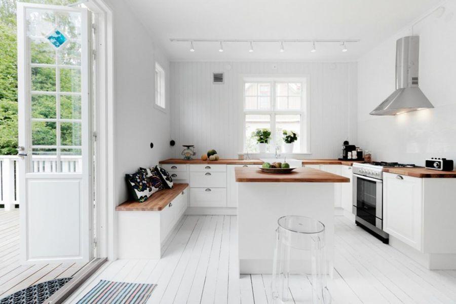 Cocina blanca y con encimera de madera y salida al jardín