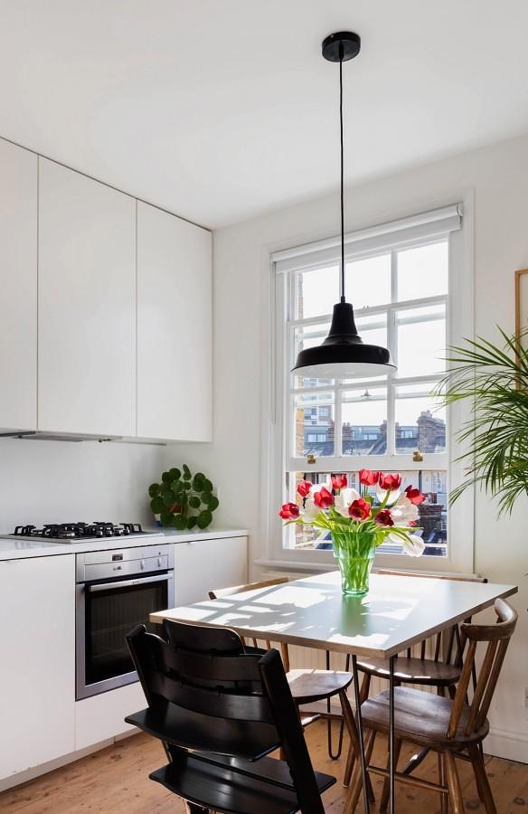 Cocina con mesa de madera y plantas