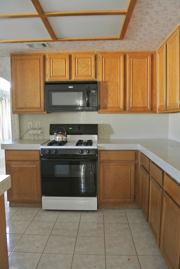 Cocina con muebles de madera y piso cerámico