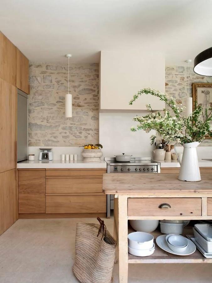 Cocina con pared de piedra y muebles de madera