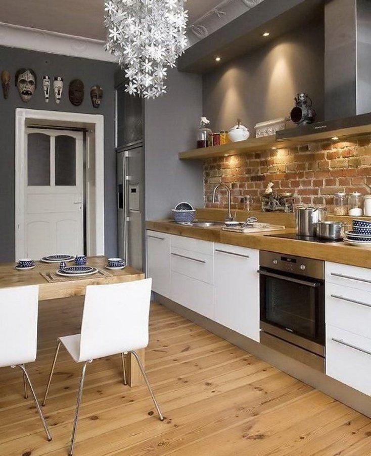 Cocina con pared de ladrillo y piso de madera