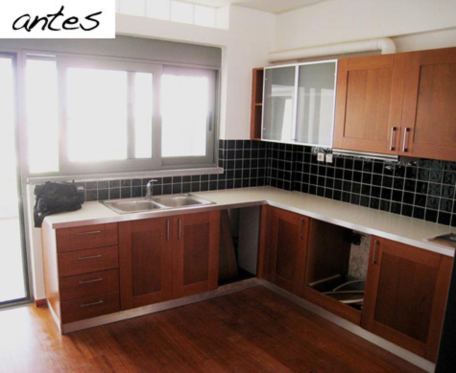Cocina con muebles de madera y azulejos negros en la pared