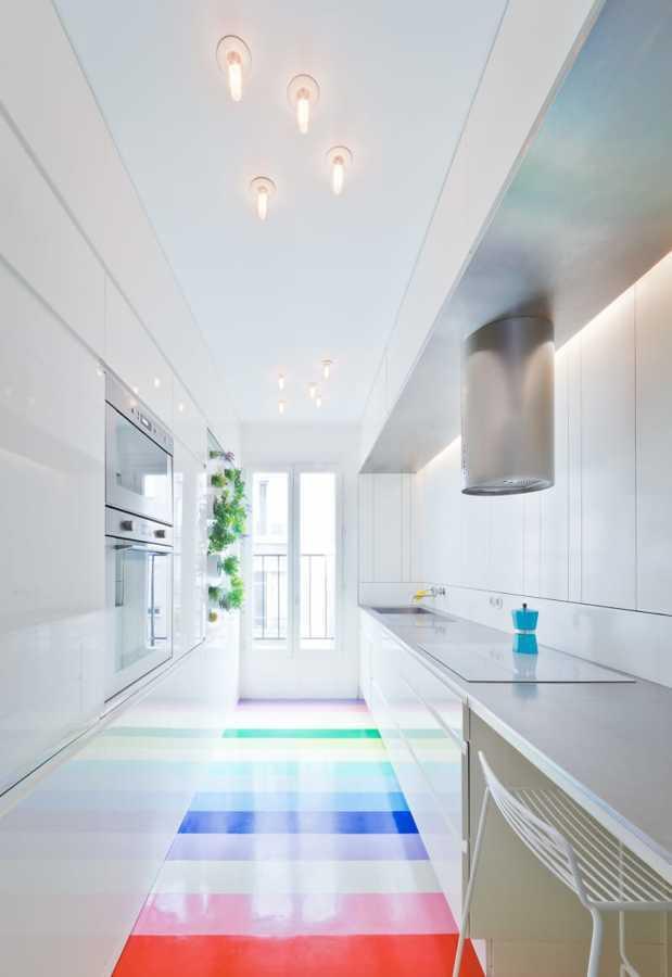 Cocina alargada con luz natural y piso de colores
