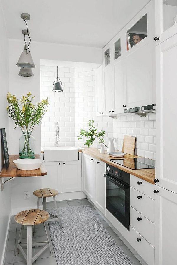 Cocina blanca con mesa auxiliar y taburetes