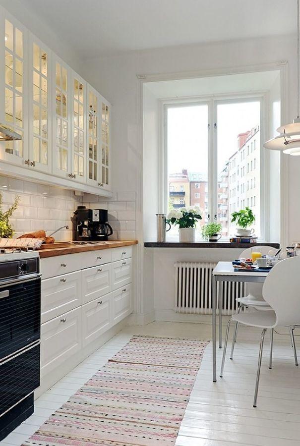 Cocina con mobiliario blanco y mesa comedor