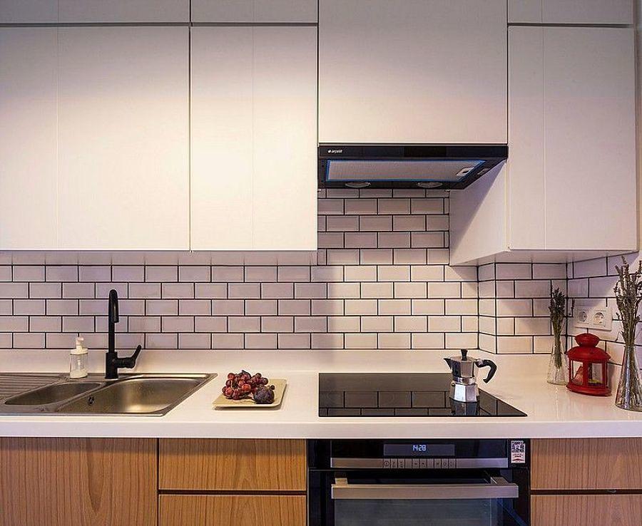 Cocina pequeña con pared de ladrillo y alacenas blancas