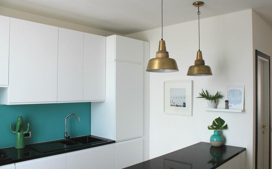 Cocina remodelada con muebles blancos y pared azul