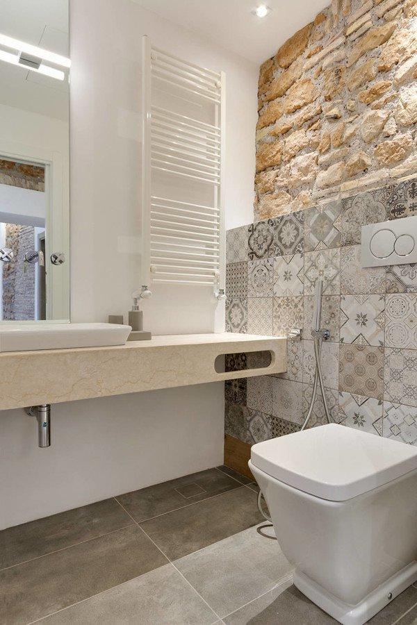 Combinación de azulejos con piedra y mármol en baño actual