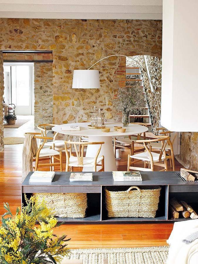 Comedor con pared de piedra y piso de madera