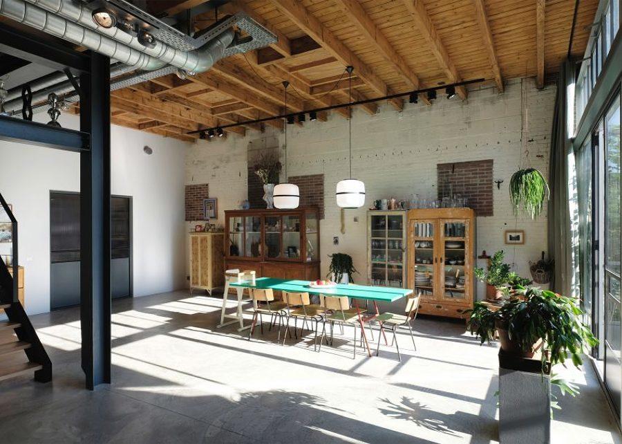 Comedor amplio con mobiliario de madera y vigas en el techo