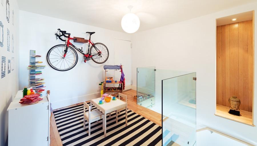 Recámara infantil con bicicleta colgada en la pared